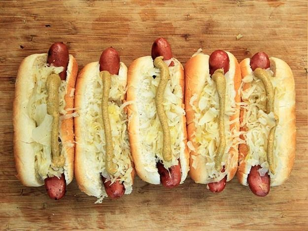 The key to perfectly cooked hot dogs on the grill is to start them in a moist bath of flavorful toppings, slow cooking them to infuse them with flavor and get an even cook, then finishing them off over the hot side to crisp and char them.