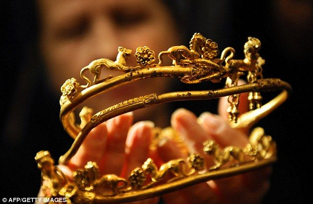 An archaeologist displays a gold tiara engraved with a lion's head and other animals found at the Bulgarian tomb. It is part of an incredible and historically-significant find...linked to Alexander the Great