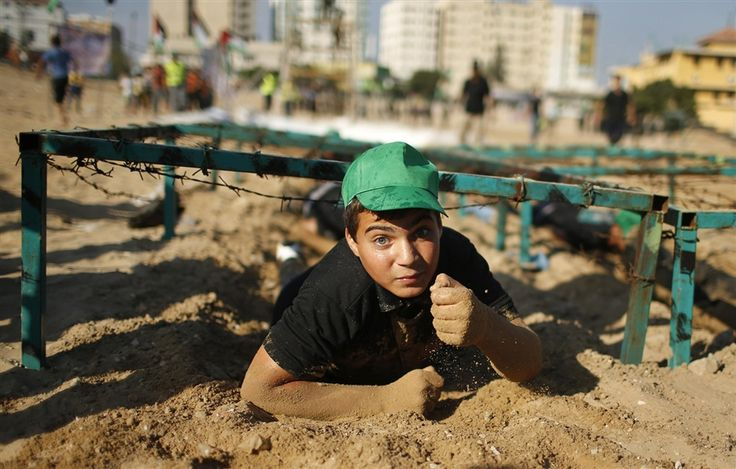 Mahmoud Haniyeh, 13, crawls during a military-style exercise at a summer camp organized by the Hamas . Tens of thousands of children from the Gaza Strip spend at least part of their holidays in special summer camps arranged around a wide array of activities. Some, organized by the United Nations, offer sports, art and dance classes. Others, laid on by Gaza's Islamist rulers Hamas, include fun and games, while seeking to reinforce religious values and awareness of the conflict with Israel.