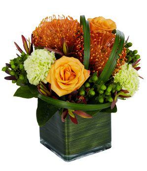 Orange roses, orange spider mums and green carnations in a modern square vase