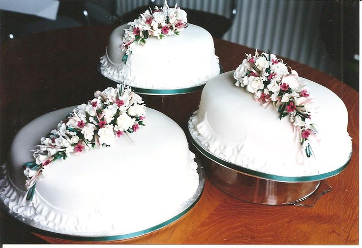 Three tier oval winter wedding cake with ivory roses, ivy and deep pink blossom.