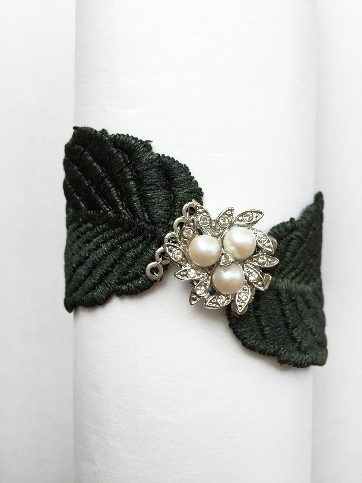Elegante brazalete fabricado de manera artesanal en encaje negro, decorado con tres piedras naturales de color blanco y cristales a su alrededor, aportando luz a la pieza.