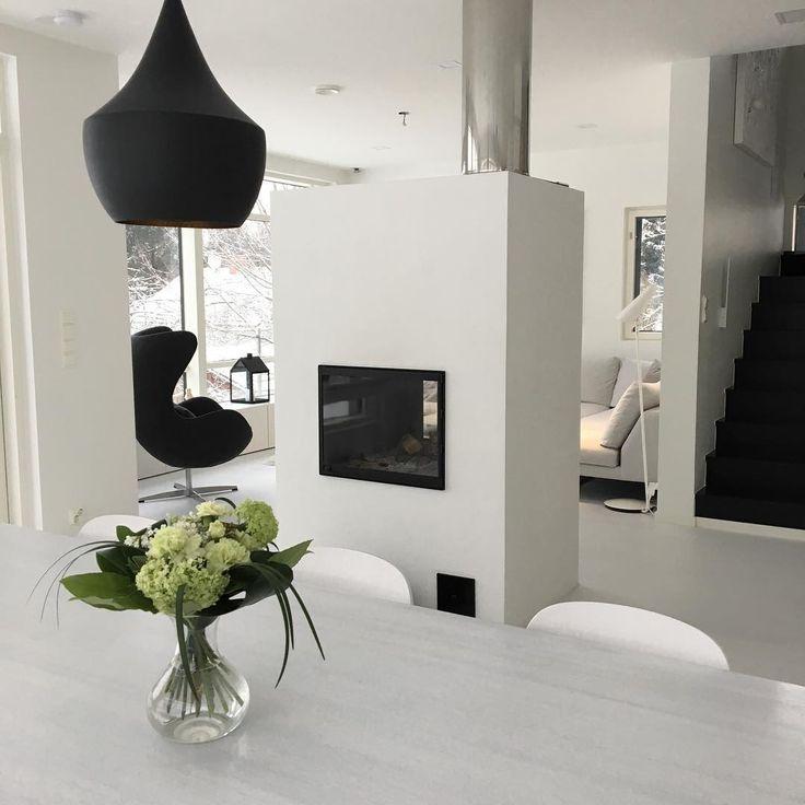 Valkoinen moderni takka tilanjakajana sekä mustat yksityiskohdat sisustuksessa