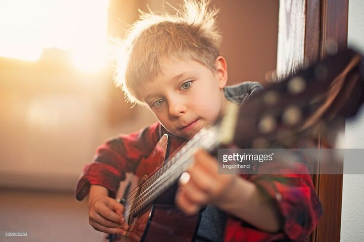Little boy practicing playing guitar near window on a sunny day. The boy aged 5 is wearing a red shirt.