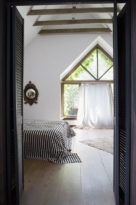 Pine Plank Flooring    Rough wood floors add character to this breezy bedroom retreat.    A large Tudor style window and exposed rafters balance the rustic appeal of the rugged pine floors. Vintage Marimekko