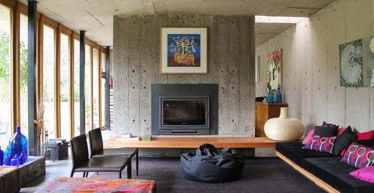 Meravigliosa villa modernista immersa nel verde in Cile. Il soggiorno è schermato dalla cucina con un'ampia colonna in cemento nella quale è collocato il camino in ghisa. A parete stampe multicolor che, insieme ai cuscini sui divani, contribuiscono a vivacizzare il living.