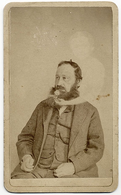 """One of the best known practitioners of spirit photography was William Mumler. In the 1860s he was one of the first photographers to claim the ability to record ""extras"" of departed spirits in photographs. He was prosecuted but never convicted of fraud. This is one of two cdvs by Mumler in our collection. The photograph shows Captain Montgomery with a spirit child."":"