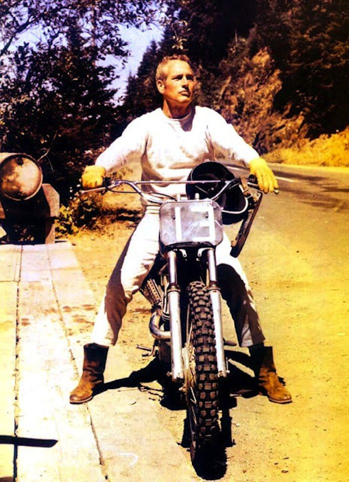 "Paul Newman — this pic is flawess. From the white jeans, to the boots, to the dirtbike. 1971 ~ Paul Newman in Oregon on the set of ""Sometimes a Great Notion,"" boning up on his off-road skills under the wing of the great J.N. Roberts – a top desert / off-road racer in the '60s – '70s. Roberts (along with his teammate Malcolm Smith, Steve McQueen, and others) tore it up onscreen in Bruce Brown's seminal (1971) motorcycle film, ""On Any Sunday."