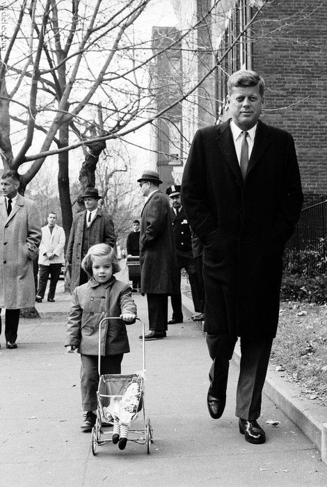 President John Kennedy with daughter, Caroline, pushing Raggedy Ann in her baby stroller.