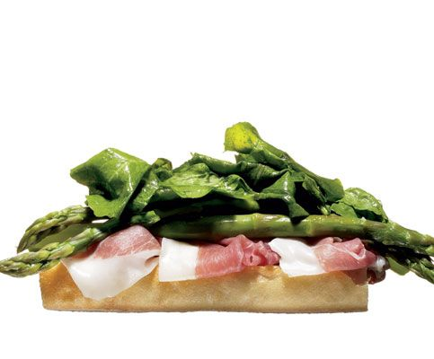 Open-Faced Prosciutto and Asparagus    Lay thinly sliced prosciutto on half a baguette. Top it with asparagus spears that've been steamed or grilled until quite tender. Toss some arugula with olive oil and lemon, and lay that on top of the asparagus. A little Dijon wouldn't hurt. Eat it open-faced to halve the carb load.