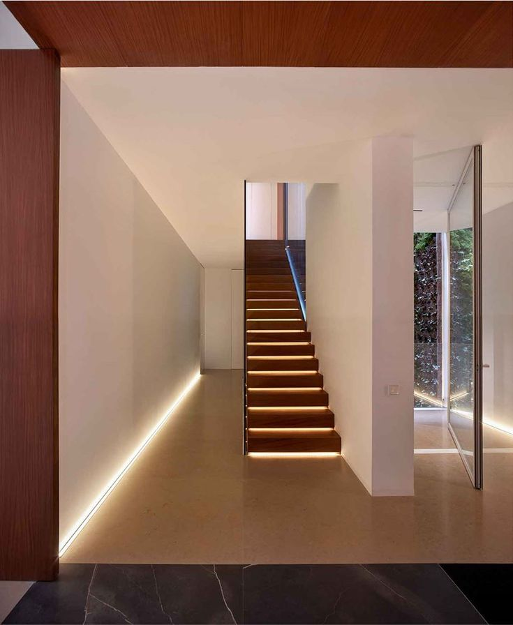 Home in the Orchard by #RamonEsteve features clean and geometric spaces, in which the perforations working as openings of the house reveal a wooden interior of great warmth, that contrasts with the purity of the rest of the facade.  Images © Fotógrafa de Arquitectura  #wood #staircase