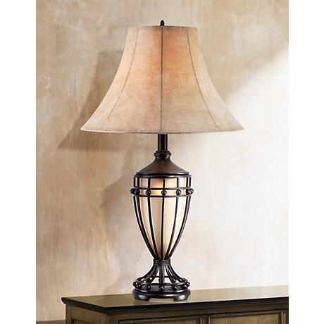 Ideal for traditional or transitional style homes, this fantastic table lamp has an outer base of brushed Cardiff iron in a design awash in lines and curves. Inside the cage-like outer base is an urn of beautiful champagne glass containing a convenient night light that also makes a great accent.