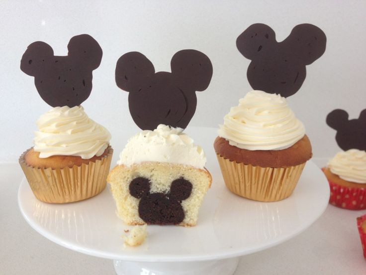 """mickey mouse cupcakes - white batter, followed by a ball, topped with a ring, of chocolate [brownie cooked and mixed with icing] then more white batter.  Piped mouse head and ears with chocolate onto parchment with design under it - add chocolate """"pick"""" to bottom of head for inserting into the cupcake.  Leave mouse outlined or fill it in as shown."""