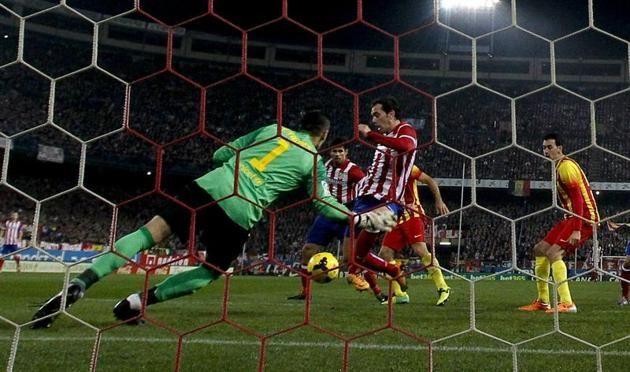 GRA261. MADRID, 11/01/2014.- El portero del FC Barcelona Víctor Valdés (i) intenta parar el lanzamiento de un jugador del Atlético de Madrid...
