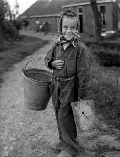Kinderen op het platteland. Een lachende boerendochter met hoofddoek om houdt onder andere een zinken emmer om haar arm. Op de achtergrond het erf met de boerderij. Nederland, zonder plaats , 1953. Ter wille van de reproductie in de Beatrijs zijn de tanden met wit opgehoogd (retouche).