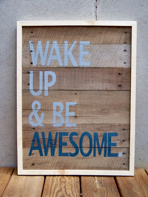 """Pieces of a recycled wooden shipping pallet were cut, lightly sanded, painted in washes of brown acrylic paint and assembled into the """"canvas"""" for this original piece of art. The message """"WAKE UP & BE AWESOME"""" was then carefully hand painted on the wood planks. The colors used are a medium shade of gray and navy blue. A hand made natural wood frame completes the piece."""