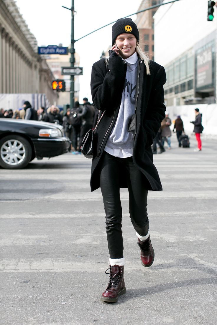 This model's kicking it old school with Doc Martens and a smiley-faced beanie.