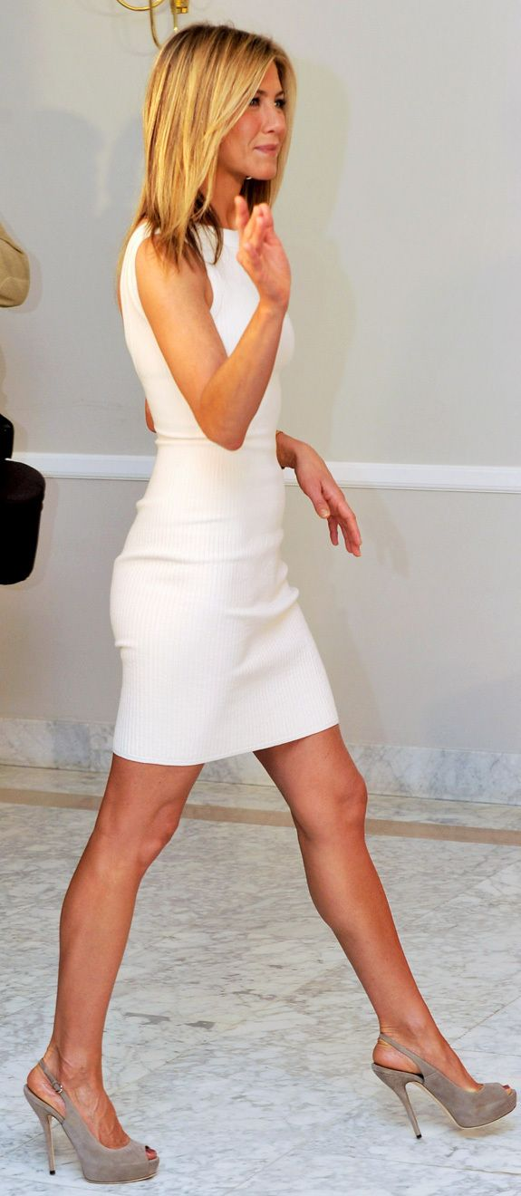 """Jennifer Aniston was all smiles during a photocall in Spain on Tuesday, but with that figure, who wouldn't be smiling?    Aniston and """"Bounty Hunter"""" costar Gerard Butler are during a European press tour for the film, cuddling up on red carpets and looking generally gorgeous everywhere they go.    Aniston's snug white sheath and Gucci heels on Tuesday was no exception."""