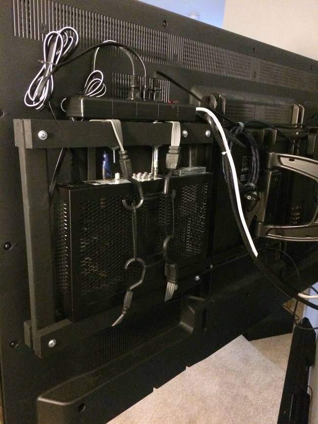 If you have a mount for your TV, fasten all of the electronics with the unsightly wires to it. (If you need to, build a small lightweight frame to attach to your mount.) Bundle up the wires as much as possible before fastening them to the mount so they don't get tangled once they're up there. Use bungee cords to secure heavier hardware like a cable box or router. Plug everything into a power strip so you only have to worry about one wire running from your TV to the wall.