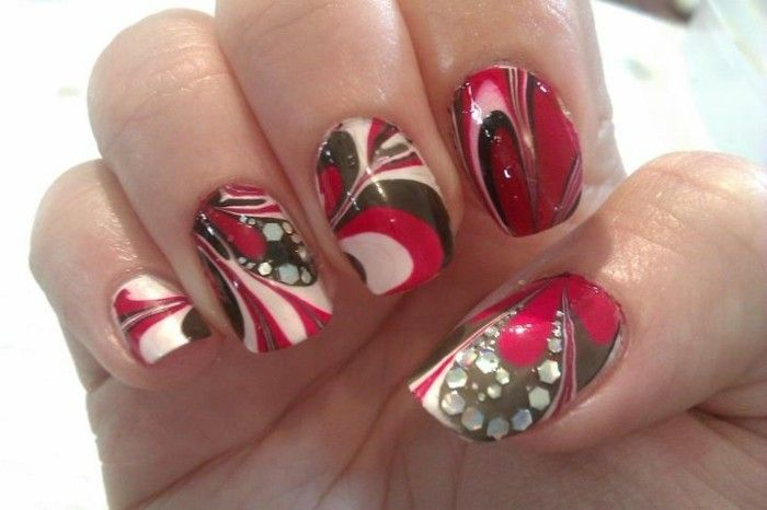 close up of hand with marble-effect nail polish, red brown and white, decorated with tiny rhinestones