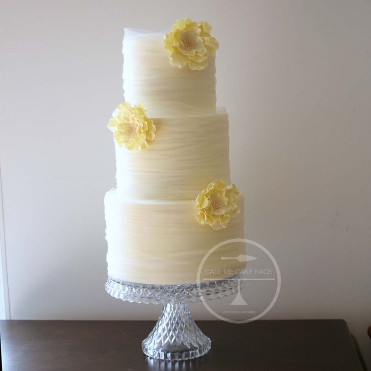 Pretty wedding cake wrapped in soft hand dyed yellow tulle and adorned with yellow ruffle sugar flowers.