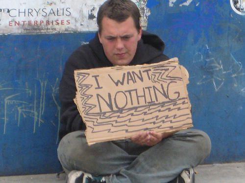 sign held be a seemingly despondent homeless young man