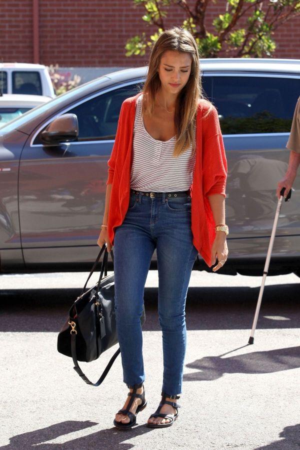 Jessica Alba está llevando los jeans, una camiseta blanca, y un suéter rosado. Los jeans cuestan cincuenta y nueve euros.  La camiseta cuesta quince euros y el suéter cuesta cuarenta euros.