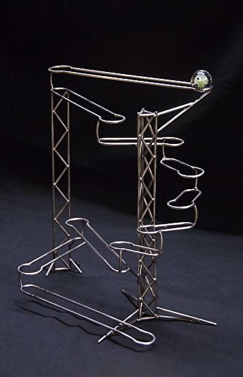 """Stainless steel kinetic sculpture, rolling ball sculpture, hand-formed and TIG-welded, powered by gravity and one 1"""" handmade glass marble, 11 3/8"""" x 11 1/2"""" x 5 3/4"""", """"Dropping In"""" by Tom Harold $325."""