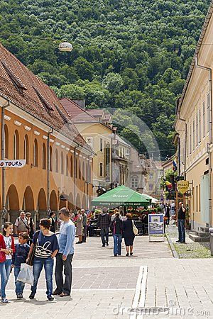 Unidentified tourists strolling down the old paved streets in the Historical Center of Brasov, the most visited touristic city in Romania.