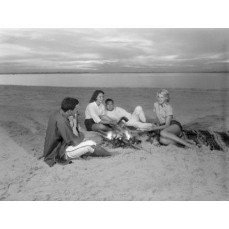 Group of young friends resting by bone fire on sandy beach Canvas Art - (18 x 24)