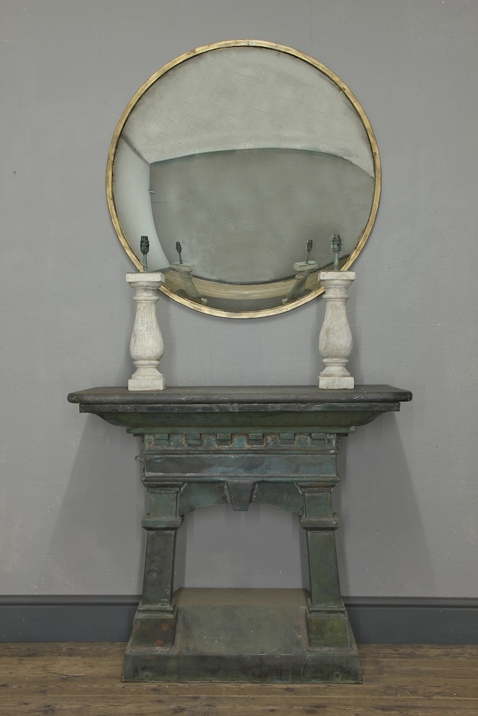 The Oculus Convex - A contemporary, steel framed mirror with distressed convex plate. Shown here with an aged gilt finish, above a C19th copper console table.