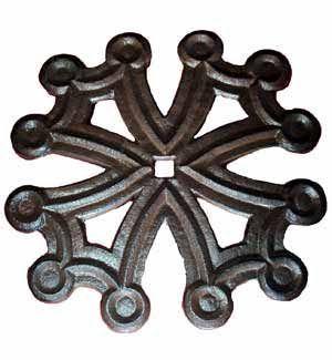 Croix occitane en fonte. C'est un dessous de plat avec pieds en caoutchouc. Couleur rouille.                             Diamè