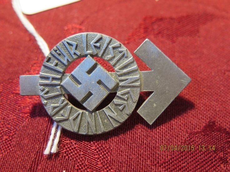 """WWII GERMAN NAZI HITLER YOUTH MEDAL/PIN Hitler Youth Proficiency Badge in Bronze The badge depicts the arrow-shaped """"Tiwaz"""" Rune, representing the Norse God of War. The rune bears the words """"For proficiency in the HJ."""" The badge is in GOOD condition. The reverse is hallmarked RZM M1/34. There is no membership number, so I am not sure if this was in distribution."""
