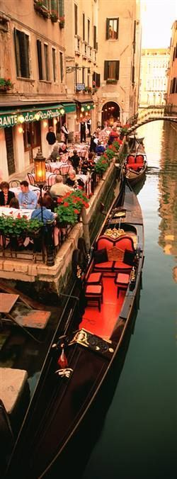 Gondolas alongside a cafe in Venice, Italy.