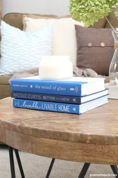 The costal rustic living room reveal - gorgeous beachy coastal living room with budget-friendly decorating and DIY projects. These blue and white coffee table books are perfect for a costal vibe. And love that neutral candle!