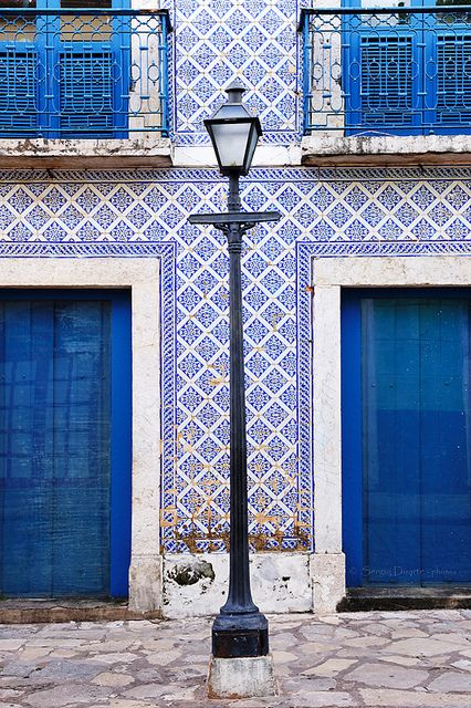 Street lamp with house with with blue doors, windows and balcony in historic center of S. Luis do Maranhão, Brasil