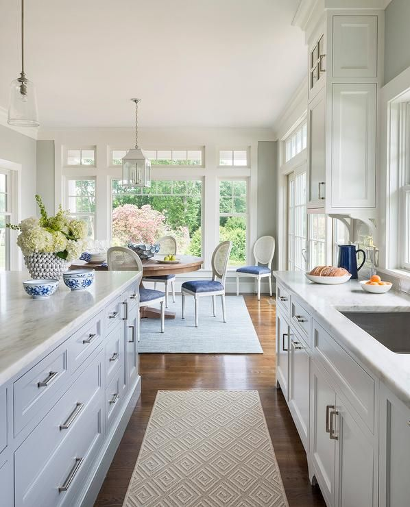 White and grey kitchen features white cabinets paired with white marble countertops fitted with a ...