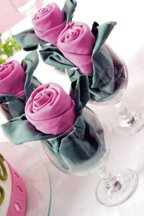 Un pliage en forme de bouton de rose réalisé avec deux serviettes présentées dans un verre à vin