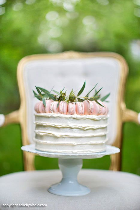 Simple white frosted cake topped with maccarons and greens