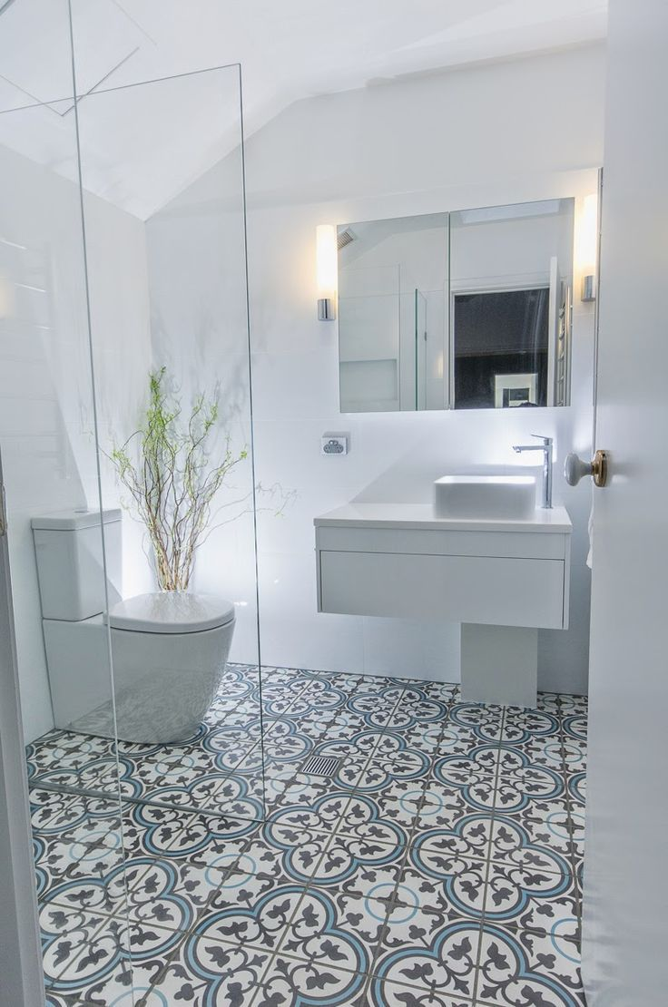 This beautiful white bathroom design has combined a modern white vanity unit and toilet with a more traditionally inspired pattern tiled floor.