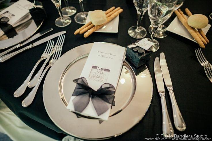 Menù di nozze nel piatto con fiocco di  tulle nero coordinato con il tovagliato. Per un matrimonio in stile classico