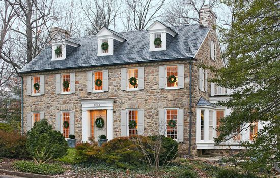 Colonial home with stone and stucco exterior accented with sash windows with pale gray shutters and a slate tiled roof framing dormer windows.