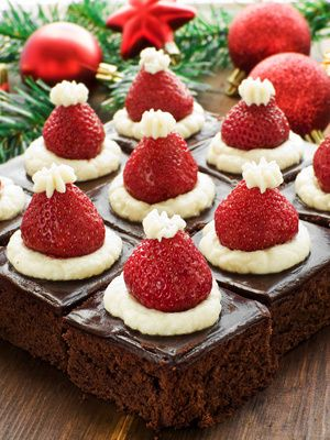 Santa hat brownies! Top each fudge brownie with a dollop of whipped cream, a strawberry, and another small dollop on top to create the Santa hat.