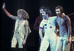 The Who on stage, standing and waving to a crowd