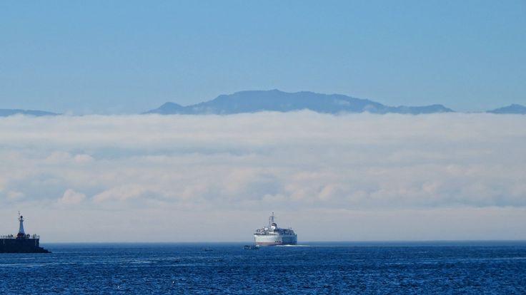 Este es un tipo de clima a menudo vemos. Aquí estamos mirando el Coho, un ferry, a medida que sale del Puerto Interior en uno de sus viajes a Port Angeles, escondidos debajo de ese banco de nubes en el horizonte. Sobresaliendo por encima de las nubes son los picos de la Península Olímpica.