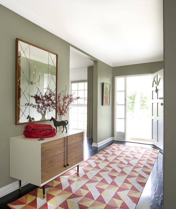 This bold rug grounds the entrance and compliments the shapes of the vintage mirror.