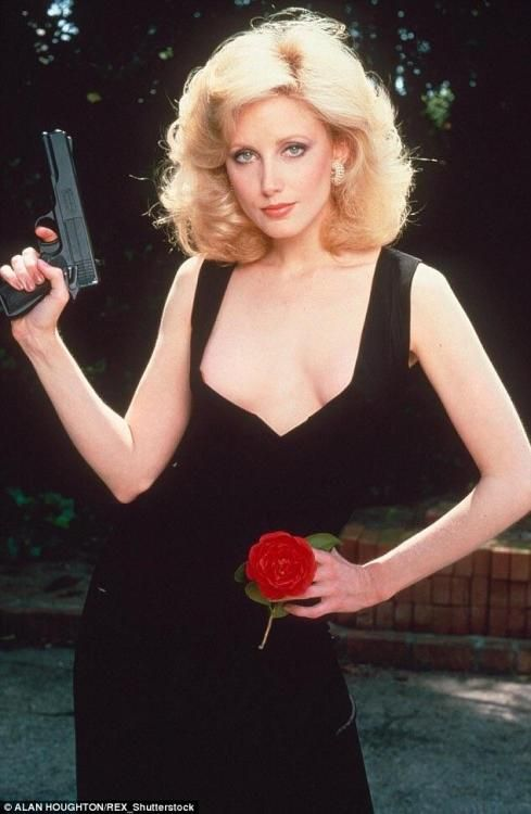 Morgan Fairchild holding a gun and a rose, 1978