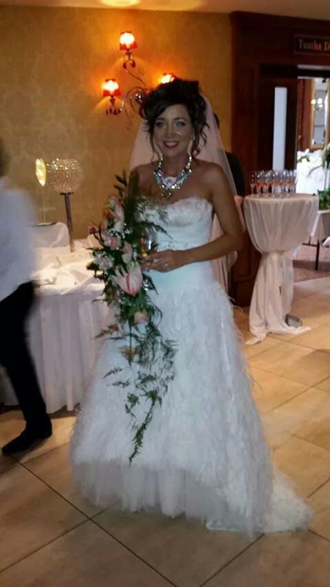 feather wedding dress with necklace and cascading bouquet