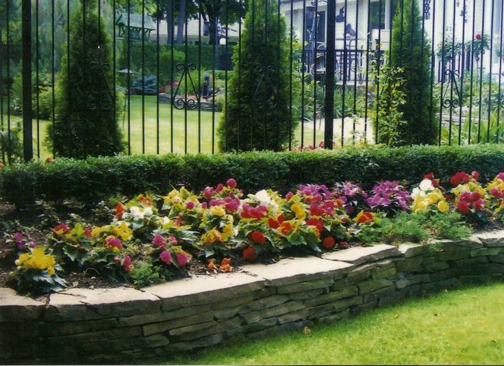 Raised flower bed along fence garden pinterest for Landscaping flower beds with stones