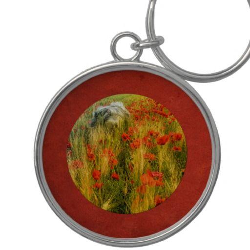Premium round keychain. Bearded collie Niki running in poppy field.